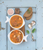 French Bouillabaisse fish tomato soup with salmon fillet, shrimp and spices on rustic wooden board over light blue Royalty Free Stock Photo