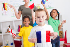 French boy. A happy little french boy holding flag in classroom with diverse nationality students in background waving flags royalty free stock photo