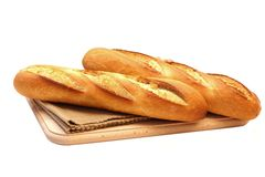 French bread. Close up of two fresh long narrow french baguettes placed on fabric mat over wooden chopping board on white background Royalty Free Stock Images