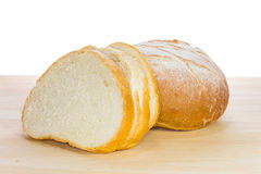 French bread. French baguette or bread in big ball shape and some slices of it on wooden table, on white background Stock Images