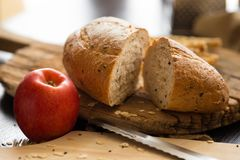 French bread baguette cut on wooden board with knife. with a cho Stock Photo