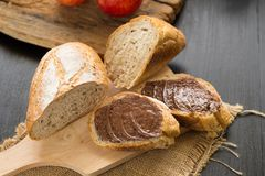 French bread baguette cut on wooden board with knife. with a cho Stock Photos