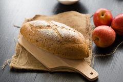 French bread baguette cut on wooden board with knife.  with red Royalty Free Stock Photography
