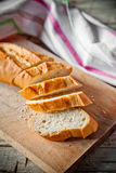 French bread baguette and linen napkin. French bread baguette cut on wooden board and linen napkin Royalty Free Stock Photo