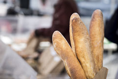French Bread. Baguettes standing in a bag at a farmer's market stall in San Francisco. People out of focus in the background royalty free stock images
