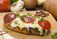 French bread pepperoni pizza. Hot fresh french bread pepperoni pizza on a cutting board with ingredients in background stock images