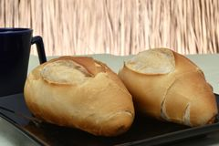 French bread, on plate with black cup in background stock photos