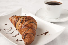 French breakfast - croissant and coffee. Sweet breakfast French style - a croissant with chocolate and a coffee on white background Royalty Free Stock Photography