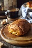 French breakfast: sweet puff pastry bun and cup of coffee. Rustic style stock photo