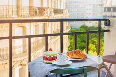 French breakfast with a view. Cup of coffee espresso, croissant and big macaron with raspberries Royalty Free Stock Image