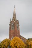 French brick church. Avery high village church in France. Cloudy day. Old architecture stock photography