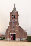 French brick church. A small, village church in France. Cloudy day. Old architecture stock photo