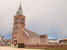 French brick church. A small, village church in France. Cloudy day. Old architecture royalty free stock images