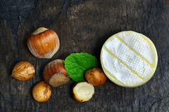 French brie cheese wheel with nuts on wooden table Stock Images