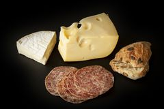 French brie and Swiss Emmental cheese with slices of salami sausage and a home baked bun on black background. Stock image royalty free stock photos
