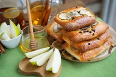 French brioche bun with pear, honey and tea on wooden table.  royalty free stock images