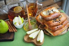 French brioche bun with pear, honey and tea on wooden table.  royalty free stock photography