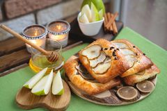 French brioche bun with pear, honey and tea on wooden table.  royalty free stock photos