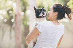 French bulldog kiss girl. French bulldog is cute kissing girl. She carry on a dog Royalty Free Stock Photography