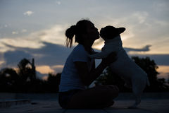 French bulldog kiss girl. French bulldog is cute kissing girl. She carry on a dog Stock Images