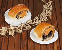 French buns with poppy seeds on saucer plate. Stock Photos