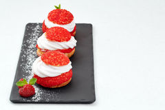 French Cakes with strawberry cream shanti. aery brewing cake on black shale. Restaurant composition on white background. Royalty Free Stock Image