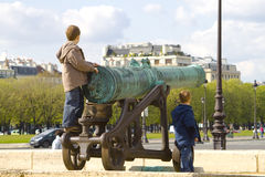 French cannon. A long cannon in the courtyard of the Invalides at Paris, with two kids playing with Stock Images