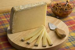 French Cantal aop cheese. On a cutting board as dessert royalty free stock photography