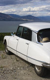 French Car Lakeside. A classic, streamlined, white French car is parked overlooking a lake Stock Photos