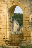 French castle through an archway. View of a French castle looking through an old brick archway Stock Photo