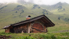 French chalet. With surrounding moutains and light fog on the top - France - The Alps - Panorama Royalty Free Stock Photo