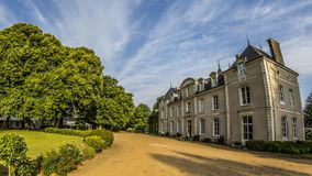 French Chateau in France under blue sky. A French Chateau with trees stands near Le Mans, June 2015, blue summer sky and clouds Royalty Free Stock Images