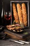 French cheese baguette with a red wine.Homemade freshly baked french baguettes. rustic style. long bread. Royalty Free Stock Image