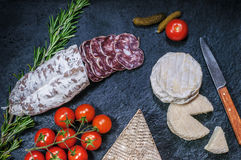 French cheese, salami, tomatoes and pickles Stock Image