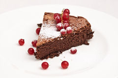 French chocolate cake. One slice of French chocolate cake served with red currant and icing sugar on a white plate Stock Image