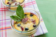 French clafoutis with blueberries and strawberries in ramekins on napkin and  turquoise wooden background Stock Photo