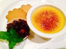 French classic dessert Creme Brulee with mixed berry compote & mint homemade cookies Royalty Free Stock Photos