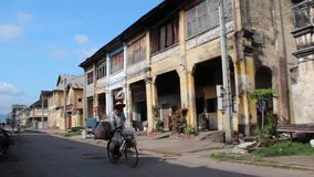 French Colonial: WS French Colonial buildings with Asian bread seller on bicycle stock footage