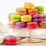 French colorful macarons in a glass cake stand. Traditional french colorful macarons in a glass cake stand on wooden table Royalty Free Stock Photo