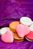 French colorful macarons with hearts on violet background Royalty Free Stock Photos
