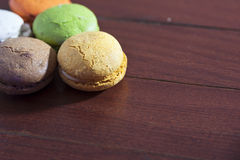 French colorful macarons on a wooden floor, morning snack Royalty Free Stock Images