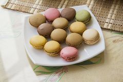 French cookies macarons. horisontal. French cookies macarons on a plate and in glass bottle Stock Photos