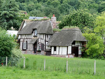 French Country Cottage. Thatched Timber Framed House and outbuilding in Normandy, France with a wooded hillside behind Stock Images