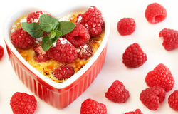 French creme brulee dessert. With raspberries and mint covered with caramelized sugar in red terracotta heart ramekin on white background Stock Images