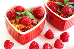French creme brulee dessert. With raspberries and mint covered with caramelized sugar in red  heart-shaped ramekins on white background Royalty Free Stock Photography