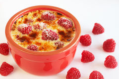 French creme brulee dessert. With raspberries covered with caramelized sugar in red terracotta ramekin on white background Royalty Free Stock Photos