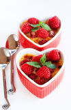 French creme brulee dessert. With raspberries and mint covered with caramelized sugar in red heart shaped ramekins on white background Royalty Free Stock Photo