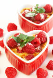 French creme brulee dessert. With raspberries and mint covered with caramelized sugar in red heart shaped ramekins on white background Stock Photography