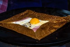 French crepe with egg, ham and cheese. French crepe cooking on the fire and stuffed with egg, ham and cheese Stock Photos