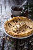French Crepes or Pancake with Banana and Chocolate. On wood background stock photos